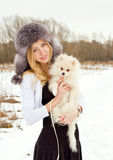 The beautiful girl the blonde in a cap with a dog  Royalty Free Stock Photo