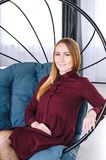 The beautiful girl in a claret dress sits on a round swing stock images