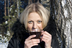 Beautiful girl blonde drinking tea in winter. In nature Stock Photography