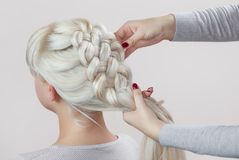 Beautiful girl with blonde hair, hairdresser weaves a braid close-up stock image
