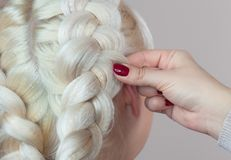 Beautiful girl with blonde hair, hairdresser weaves a braid close-up,. In a beauty salon. Professional hair care and creating hairstyles stock photo