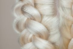 Beautiful girl with blonde hair, hairdresser weaves a braid close-up, in a beauty salon. Professional hair care and creating hairstyles royalty free stock image