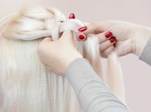 Beautiful girl with blonde hair, hairdresser weaves a braid close-up, in a beauty salon royalty free stock photo