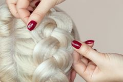 Beautiful girl with blonde hair, hairdresser weaves a braid close-up, in a beauty salon. Professional hair care and creating hairstyles royalty free stock images