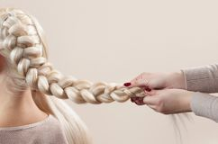Beautiful girl with blonde hair, hairdresser weaves a braid close-up. In a beauty salon. Professional hair care and creating hairstyles stock photo