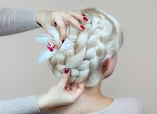 Beautiful girl with blonde hair, hairdresser weaves a braid close-up, in a beauty salon. royalty free stock photo