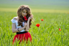 Beautiful girl on blooming poppy field Royalty Free Stock Image