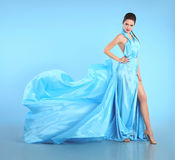 Beautiful Girl in blowing blue dress. Woman in Flying Gown, Silk Royalty Free Stock Image