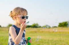Beautiful girl blowing bubbles in nature, free space. Summer background, happy childhood Royalty Free Stock Photo