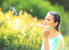 Beautiful girl blowing bubbles outdoors Stock Photography