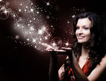 Beautiful girl blowing magic Stock Image