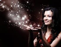 Beautiful girl blowing magic. Stars Stock Image