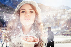 Beautiful girl blowing of snow and snowflakes, winter Stock Photography