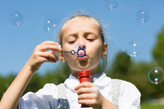 Beautiful girl blowing soap bubbles Royalty Free Stock Photo
