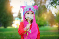Beautiful girl blowing on white dandelion, smile Stock Images