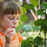 Beautiful girl blows a big bubble. Closeup beautiful girl blows a big bubble Royalty Free Stock Photo