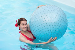 Beautiful girl with blue ball in swimming pool. Royalty Free Stock Photo
