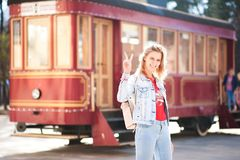 Beautiful girl in a blue denim jacket and jeans against a red tram. Woman shows the world with gestures in the sunset sun with a b Royalty Free Stock Photography
