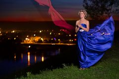 Beautiful girl in a blue dress. On the background of night city Stock Photos