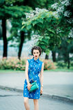 Beautiful girl in blue dress in the crosshairs with purse. Young fashion woman with a green purse in hand on city background Royalty Free Stock Photos