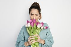 Beautiful girl in the blue dress with flowers tulips in hands on a light background.  royalty free stock image