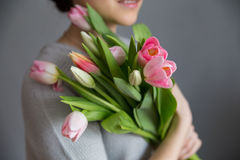 Beautiful girl in the blue dress with flowers tulips in hands on a light background Royalty Free Stock Images