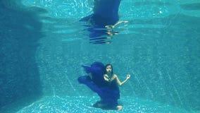 Beautiful girl in blue dress meditating under water in swimming pool. Underwater. Beautiful brunette in long blue dress dives under water in swimming pool stock video