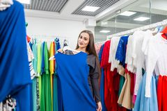Beautiful girl with blue dress near mirror on room background. Happy young woman choosing clothes in mall or clothing stock photography