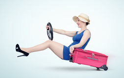 Beautiful girl in blue dress with pink suitcase drives a car. Lady goes on vacation Royalty Free Stock Images