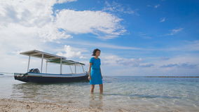 Beautiful girl in blue dress walking on the water near the moored boats. Slim brunette walks close to the sandy beach stock footage