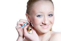 Beautiful girl with blue eyes and earring isolated. Beautiful young blond girl with blue eyes, blue nails and hands putting on golden earring with green stones stock photos