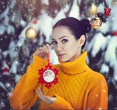 A beautiful girl with blue eyes in a yellow sweater is holding a New Year`s toy under a snow-covered tree. A girl in. Fairy-tale New Year`s decorations. Magic Stock Images