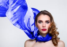 Beautiful girl with blue fashion scarf on grey royalty free stock photos