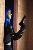 Beautiful girl with blue hair holding gun in strikeball location background Stock Images
