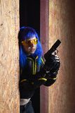 Beautiful girl with blue hair holding gun in strikeball location background Royalty Free Stock Image