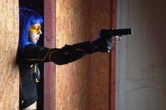 Beautiful girl with blue hair holding gun in strikeball location background Royalty Free Stock Photography