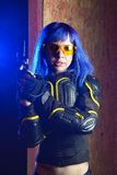 Beautiful girl with blue hair holding gun in strikeball location background Stock Photography