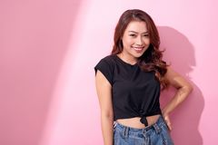 Beautiful girl in blue jeans and black shirt posing, smiling on pink background in studio.  stock image