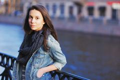 Beautiful girl in blue jeans jacket and scarf straightens hair standing near the parapet on embankment. In her hand brown elegant. Beautiful girl in blue jeans Royalty Free Stock Photos