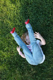 Beautiful girl in blue jeans lying on the grass and holding her legs Stock Image