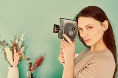 Beautiful girl in blue jeans with a retro camera th in hands on a turquoise background, look at the camera