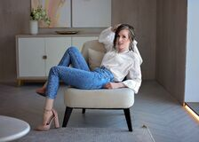 Beautiful girl in blue jeans and white shirt on a chair. Portrait of a young lady