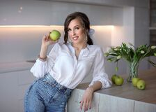 A beautiful girl in blue jeans and a white shirt holds a green Apple. Portrait of a young lady