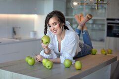 A beautiful girl in blue jeans and a white shirt is lying on a table with green apples. Portrait of a young lady