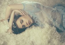 Beautiful girl in blue nightgown falling asleep. Young female with brunette hair lying on soft white feathers. Tenderness and airiness concept Stock Images