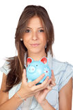 Beautiful girl with a blue piggy-bank Stock Photography