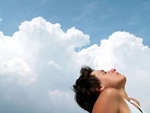Beautiful girl on blue sky. Girl on white clouds and blue sky looking to the future royalty free stock photography