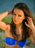 Beautiful girl in blue swimsuit posing on the beach Royalty Free Stock Photos