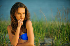 Beautiful girl in blue swimsuit posing on the beach Stock Images