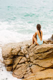 Beautiful girl in blue swimsuit sit on big stone. Stock Image